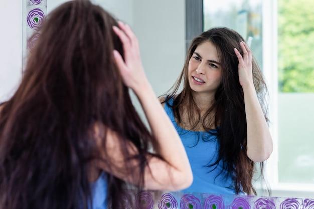 Morena sonriente mirando su reflejo en el espejo en el baño