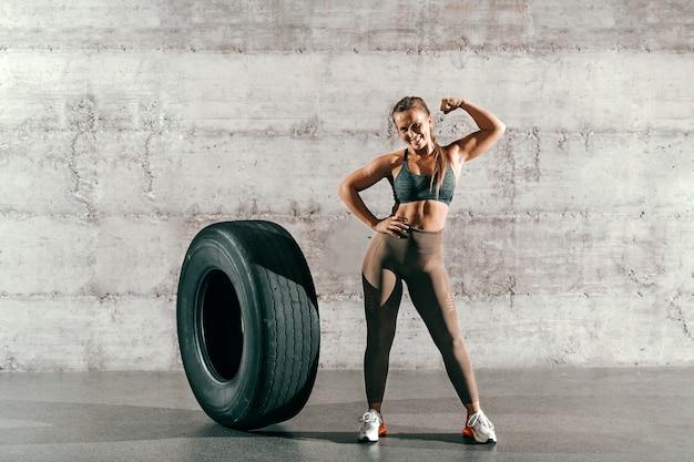 Morena sonriente muscular con cola de caballo y en ropa deportiva posando junto a un neumático grande frente a la pared gris en el gimnasio.
