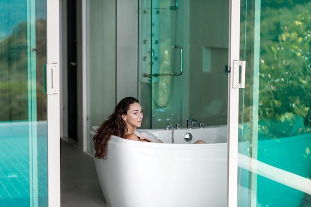 Morena sonriente posando mientras está acostado en un baño de espuma cerca de una ventana abierta