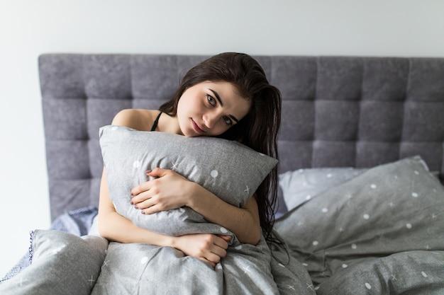 Morena sonriente sentada en la cama en su casa en el dormitorio