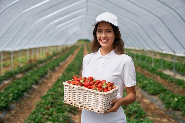 Morena sonriente sostiene una cesta de fresas