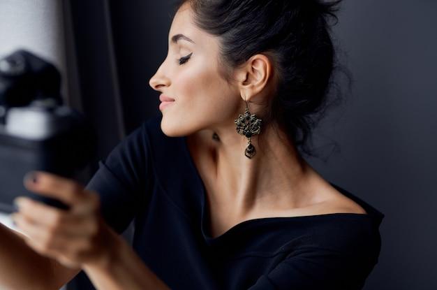 Morena sosteniendo una cámara cerca del estilo elegante de la moda de decoración de la ventana