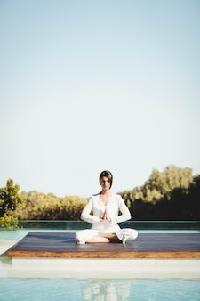 Morena tranquila haciendo yoga junto a la piscina.