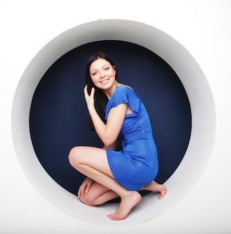 Morena con vestido azul sentada en un círculo