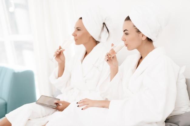 Morenas en batas de baño blancas se divierten en una habitación luminosa.
