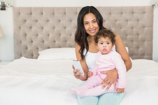 Morenita sonriente que detiene a su bebé y que usa smartphone en la cama