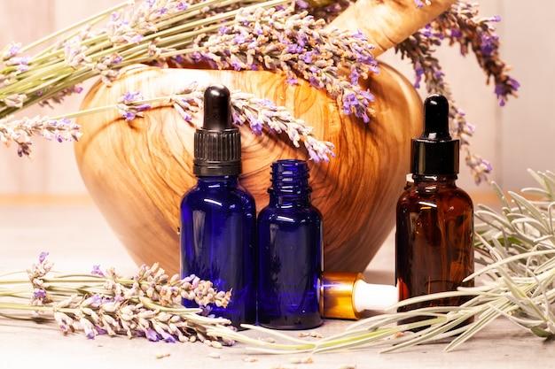 Mortero y mano de lavanda y botellas de aceites esenciales para aromaterapia.