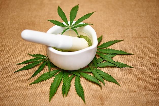 Mortero con polvo de cannabis y hojas de cannabis en el espacio de arpillera.