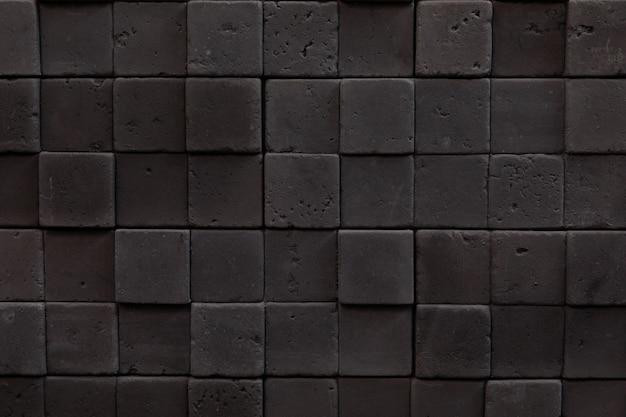 Mosaico de primer plano de piedras cuadradas oscuras, decoración interior en estilo loft, hormigón