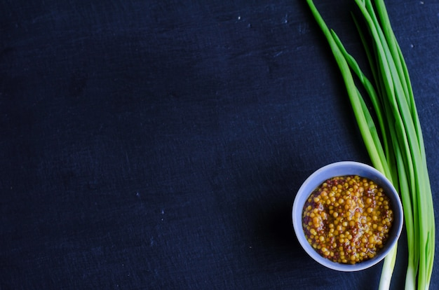 Mostaza dijon en un pequeño plato de salsa con cebolla tierna sobre pizarra negra