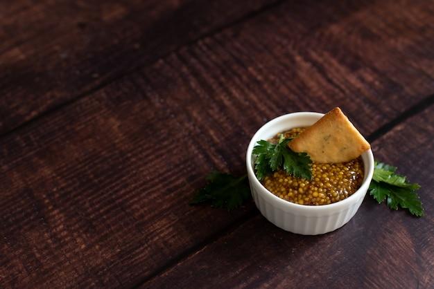 Mostaza de grano entero gastrónoma en la salsa de la salsa blanca aislada en fondo de madera. vista superior