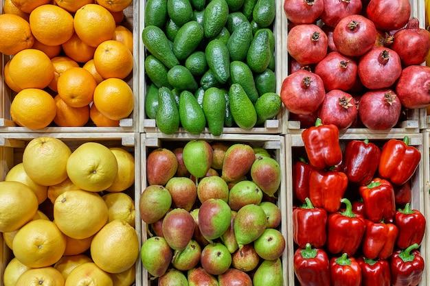 Un mostrador con diferentes verduras en los cajones se presenta de manera hermosa y uniforme desde arriba. zanahorias papas pepinos, pimientos, cebollas, tomates.