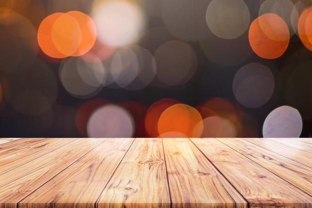 El mostrador de madera de la mesa en la ciudad de la noche enciende el fondo del bokeh, las luces enmascararon el fondo borroso del bokeh