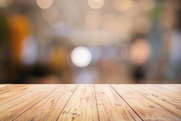 El mostrador de mesa de madera en la noche de la ciudad enciende el fondo del bokeh, las luces enmascararon el fondo borroso del bokeh para el producto del montaje