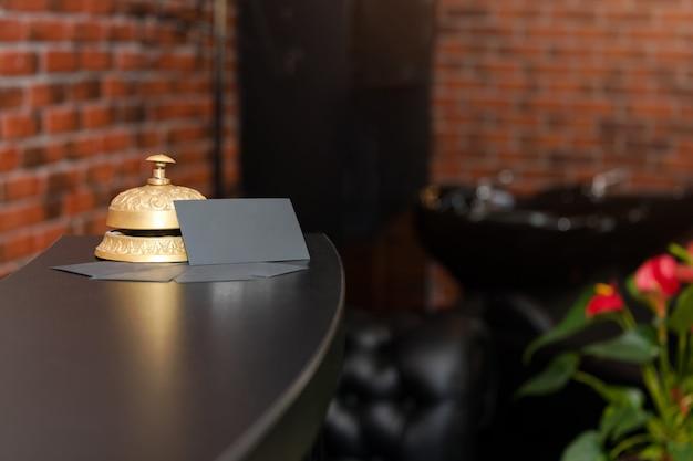 Mostrador de recepción del hotel con campana de servicio. el conserje del hotel llama al timbre