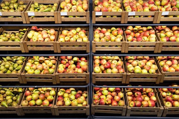 Mostrador de supermercado con muchas cajas de madera con manzanas y peras frescas