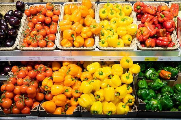 Mostrador de la tienda de comestibles con cestas de mimbre y cajas de lug con tomates, calabaza, pimiento naranja y amarillo y berenjenas