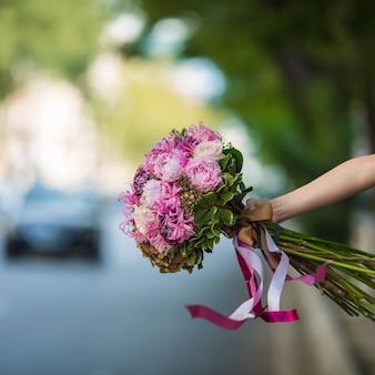 Mostrando un ramo púrpura de rosas y flores de seda en la vista de la calle