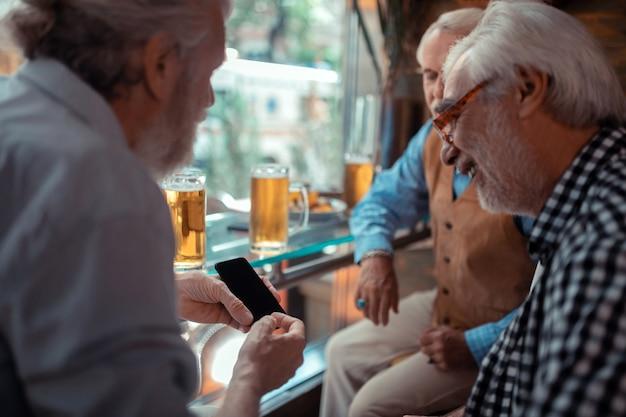 Mostrando teléfono inteligente. hombre canoso con barba mostrando smartphone mientras bebe cerveza con amigos