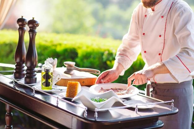 Mostrar cocina. el cocinero prepara a la familia carpaccio para los huéspedes del restaurante.