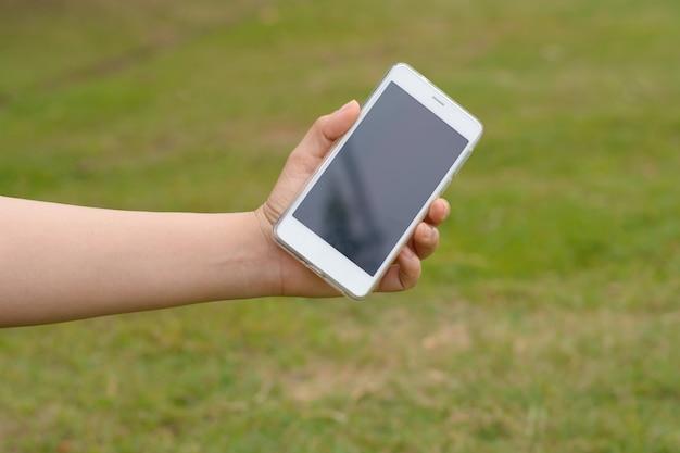 Mostrar mi teléfono móvil inteligente al aire libre en el parque