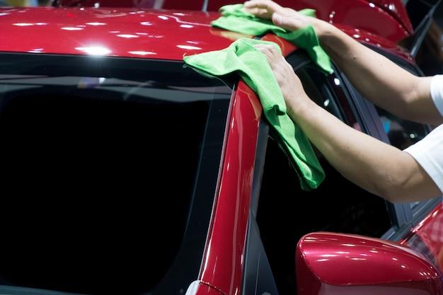 Motion of man limpia el coche rojo.