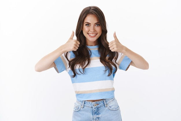 Motivada y atractiva mujer joven afortunada que apoya y acepta una gran idea, muestra el pulgar hacia arriba sonriendo al juzgar, recomienda un producto de buena calidad, acepta y aprueba un excelente servicio