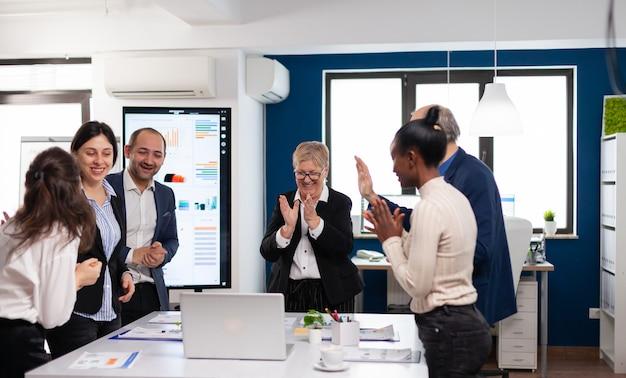 Motivado feliz equipo de negocios diversos personas aplaudiendo celebrando el éxito en la reunión corporativa