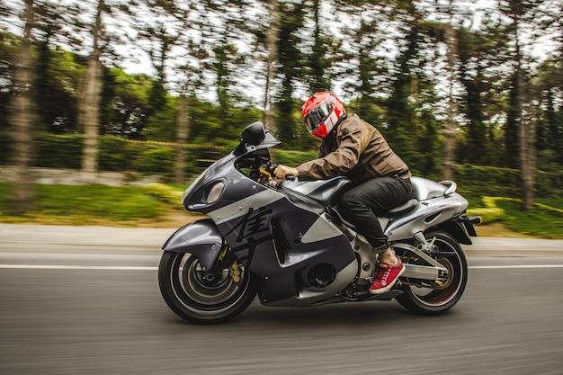 Moto de alta velocidad en bicicleta por la carretera a través del bosque