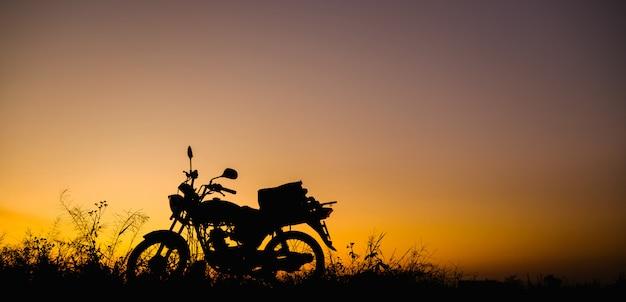 Motocicleta en el atardecer y el amanecer con espacio de copia. moto silueta