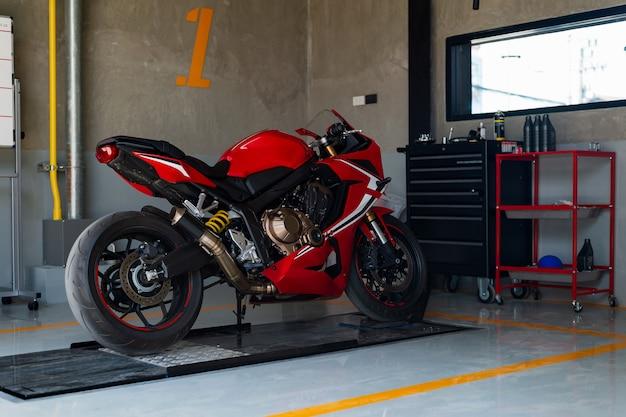 Motocicleta deportiva de primer plano en estación de reparación y taller de carrocería.