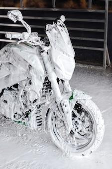 Una motocicleta en jabón en los lavados de autos.