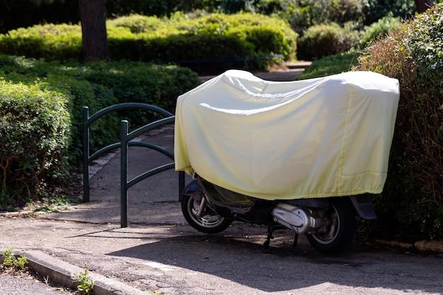 Motocicleta negra cubierta con una cubierta amarilla en las calles de la ciudad