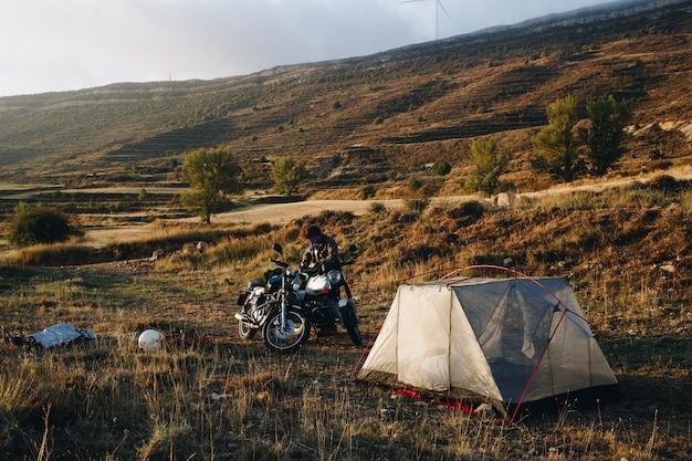 Motociclista de aventura acampando en la naturaleza