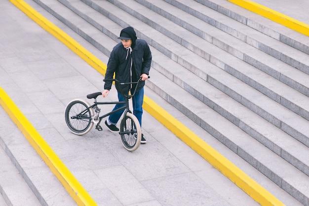 Un motociclista de bmx está parado en las escaleras y mirando de lado a lado. vista superior. camina con una bicicleta. cultura callejera