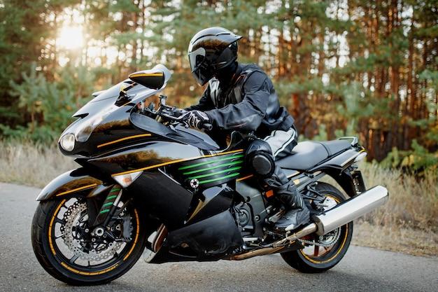 El motociclista cabalga por un camino forestal. diviértete en una carretera vacía en una motocicleta deportiva. copie el espacio para su texto personalizado