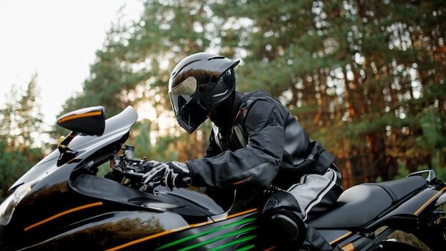 El motociclista en un casco y equipo de protección de cuero de cerca parece recto, sentado en una motocicleta deportiva rápida