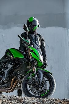 Motociclista en un casco y un traje de protección se encuentra debajo del puente