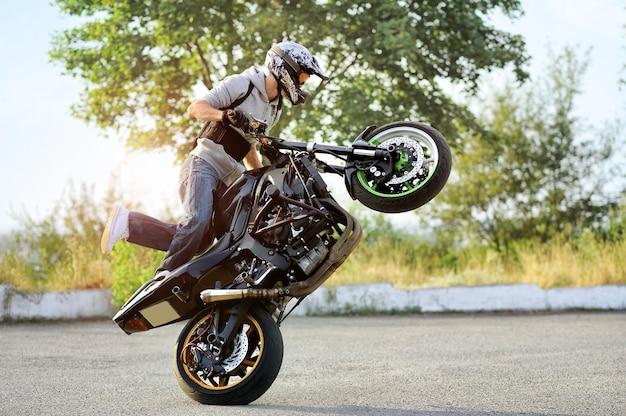 El motociclista está conduciendo una motocicleta de manera extrema.