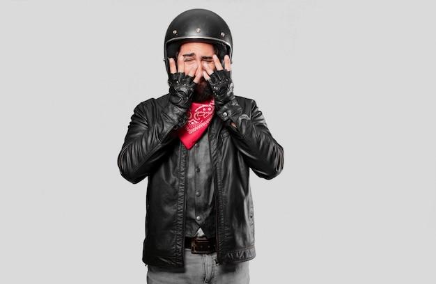 Motociclista llorando triste