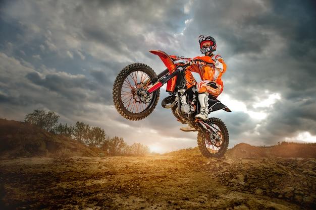 Motociclista profesional que conduce en las montañas y más abajo en la pista todoterreno.