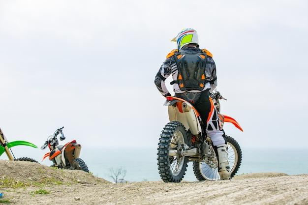 Motociclista en un traje protector sentado en moto