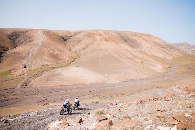 Motociclistas que conducen a través de una pista pedregosa de algunas montañas del desierto