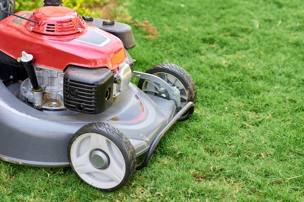 Motor de césped sobre hierba verde en un jardín cerca