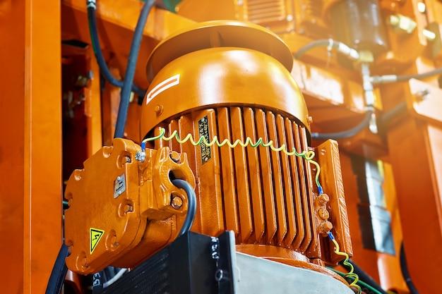 Motor eléctrico naranja con cables y mangueras en el fondo de la construcción de ingeniería pesada