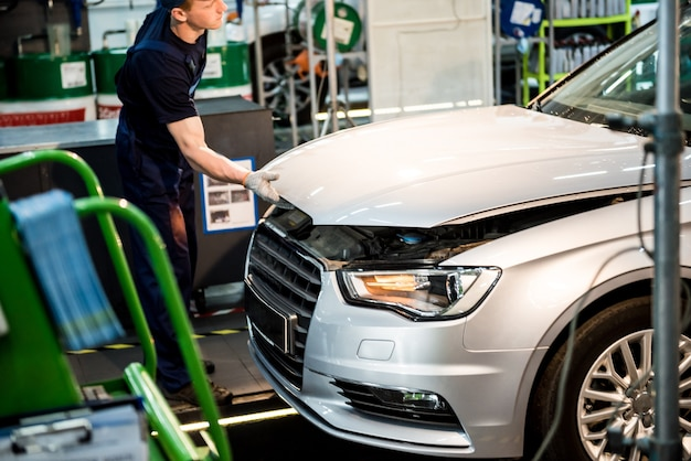 Motor de reparación de mecánico de automóviles en la estación de servicio. reparación de autos.