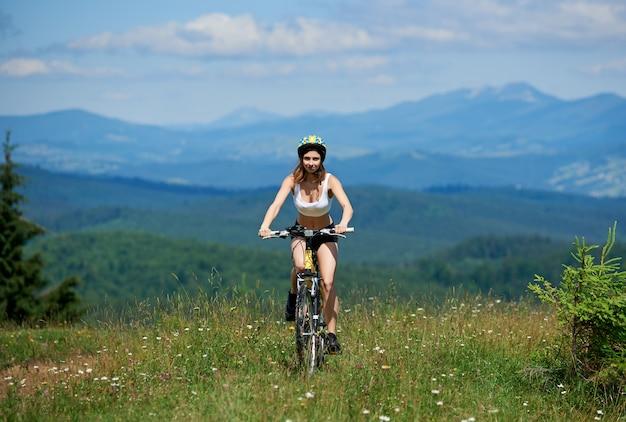 Motorista activo de la muchacha que monta en la bici de montaña amarilla en una hierba, el día soleado. montañas, cielo azul. actividad deportiva al aire libre