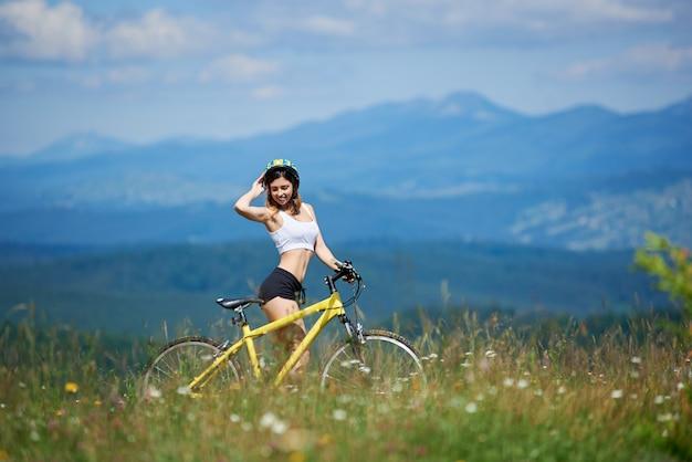 Motorista femenino deportivo joven que se coloca con la bicicleta amarilla de la montaña en una hierba, el día de verano. montañas y cielo azul en el fondo. actividad deportiva al aire libre.