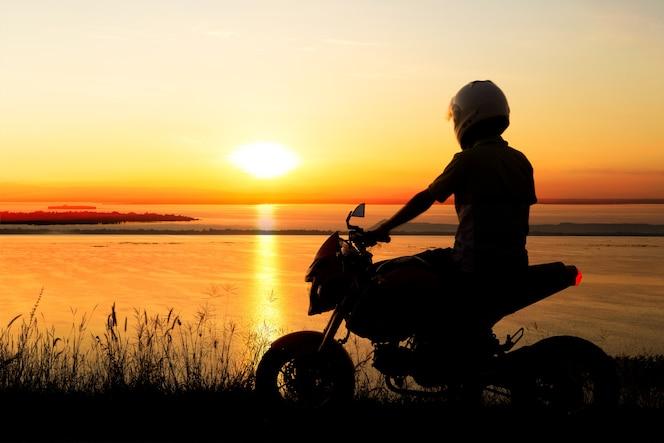 Motorista joven sobre la puesta del sol, motocicleta que monta masculina, conductor de la moto que viaja