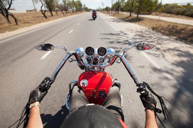 Motorista que monta la motocicleta en el camino en día soleado de la mañana. disparo desde atrás